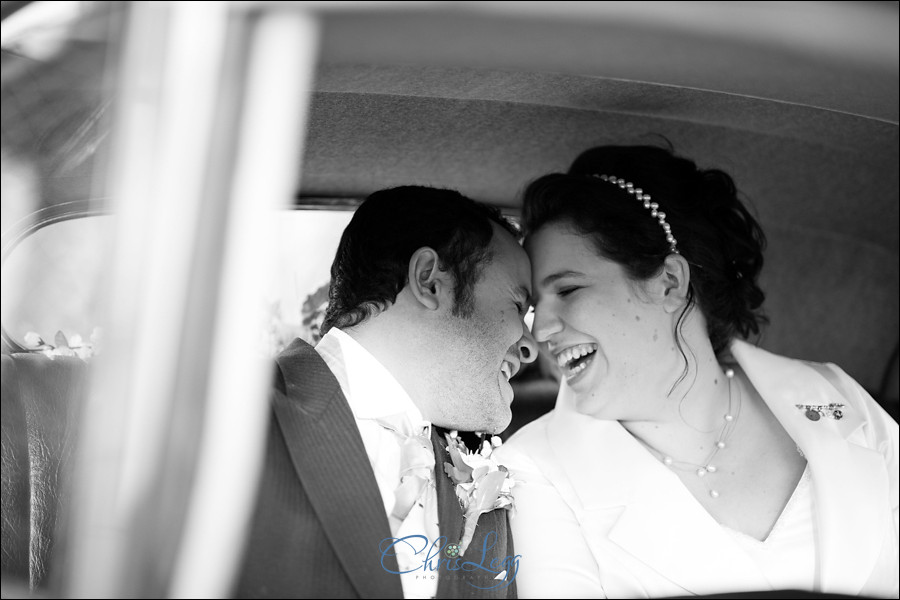 Bride and groom laughing in car after wedding ceremony