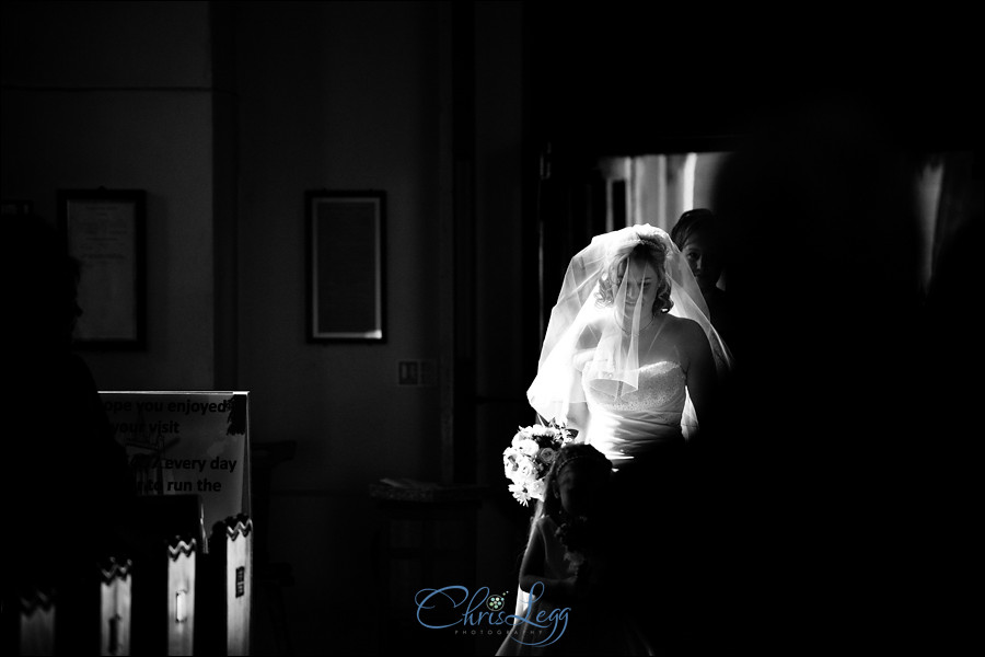 Black and white shot of bride walking up the aisle
