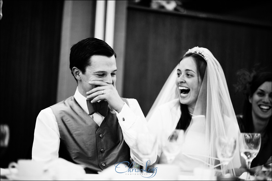Bride and groom laugh during the speeches