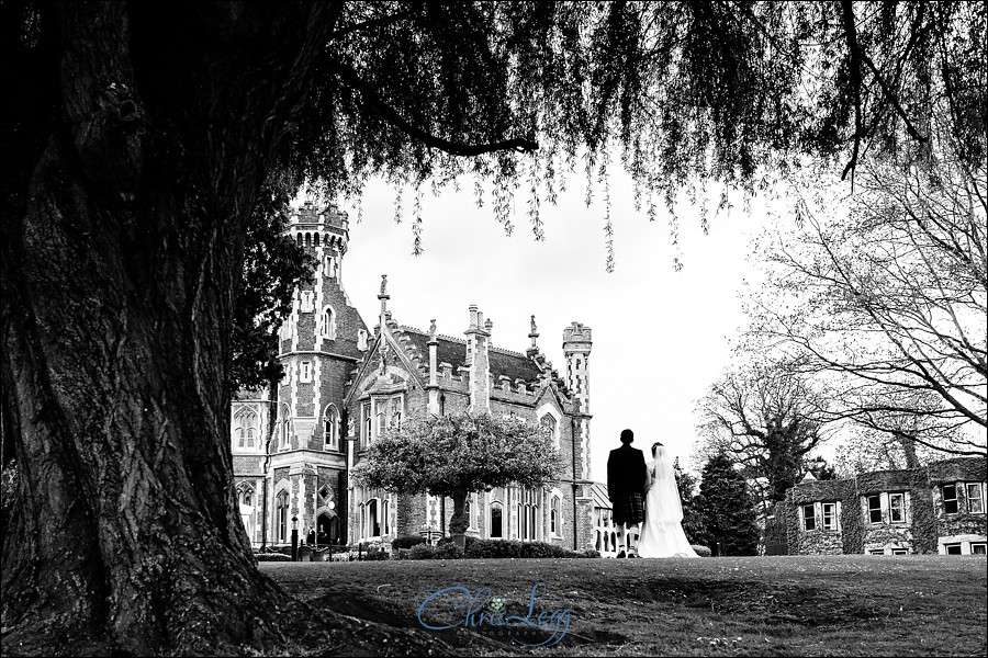 Black and white image of bride and groom standing outside Oakley Court Hotel