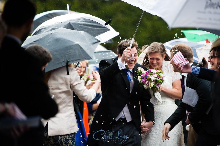 Bride and groom battle the rain as they leave the church