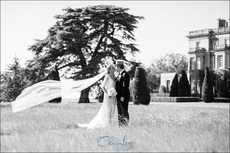 Black and white image of bride and groom standing outside Hedsor House