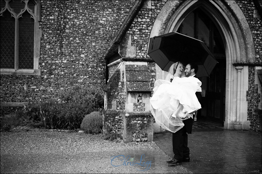 Bride being carried by groom as they leave the church in the rain