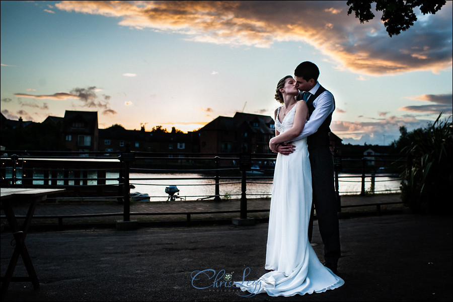 Bride and groom stand together as the sun sets in Windsor
