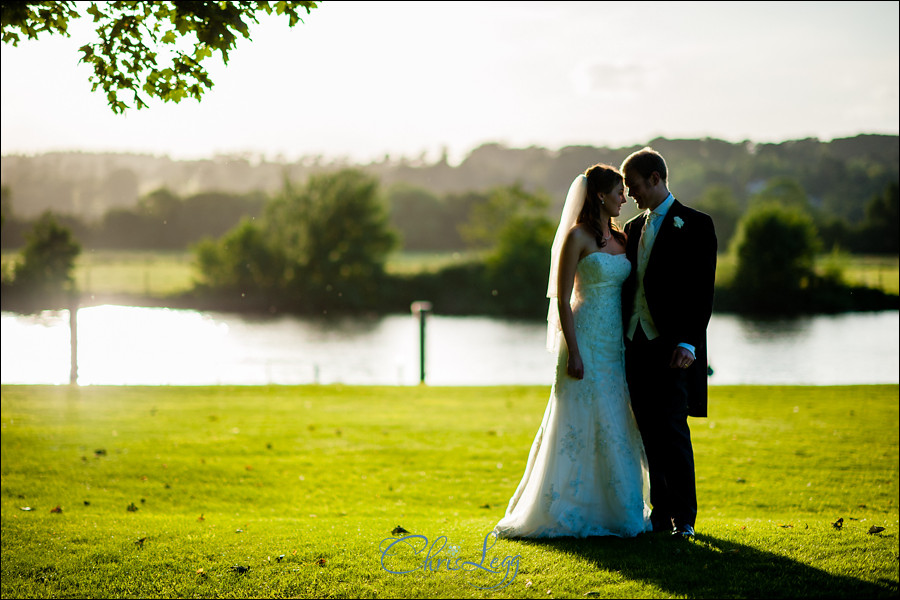 Bride and groom in the late afternoon sun by the Thames at Bisham Abbey