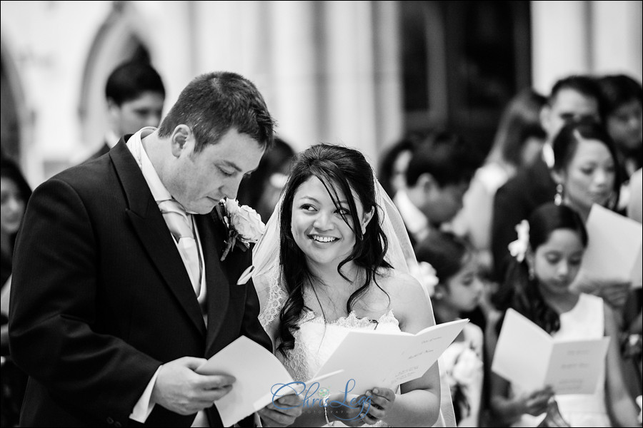 Black and white image of a bride and groom during the ceremony at Sacred Heart in Wimbledon