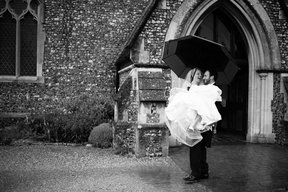 Wedding Photographer in Berkshire of the Bride and Groom leaving the church in the rain